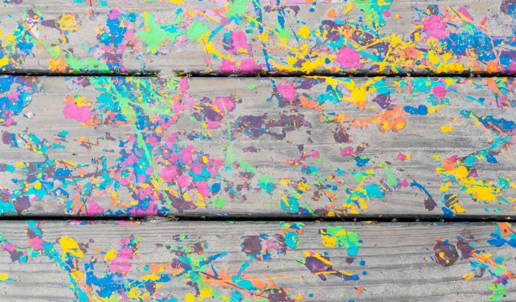 Planks of wood stained with colourful paint splatter